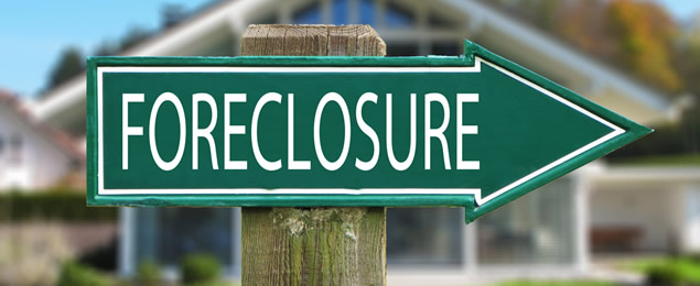 Sign posted on post pointing the way to foreclosure home listings.