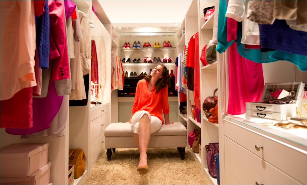 Woman admiring her clothes in large walk-in closet of her new home.