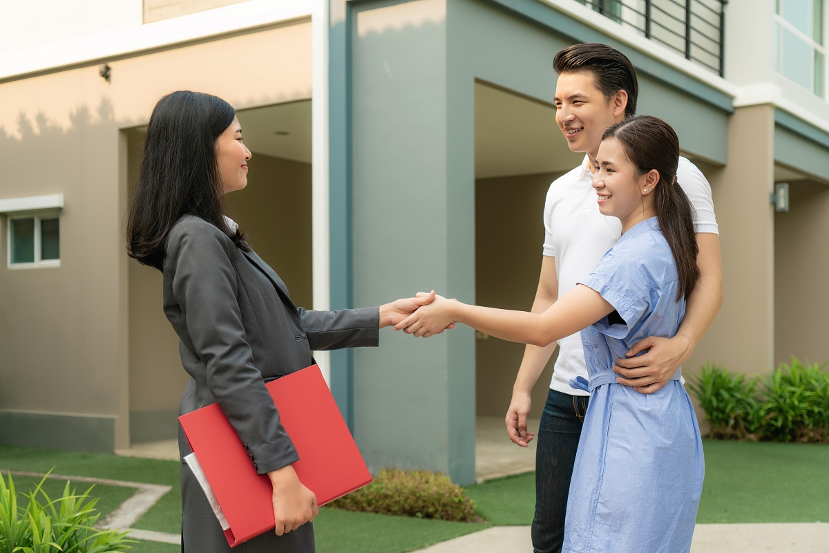 Happy Asian couple looking at house with realtor
