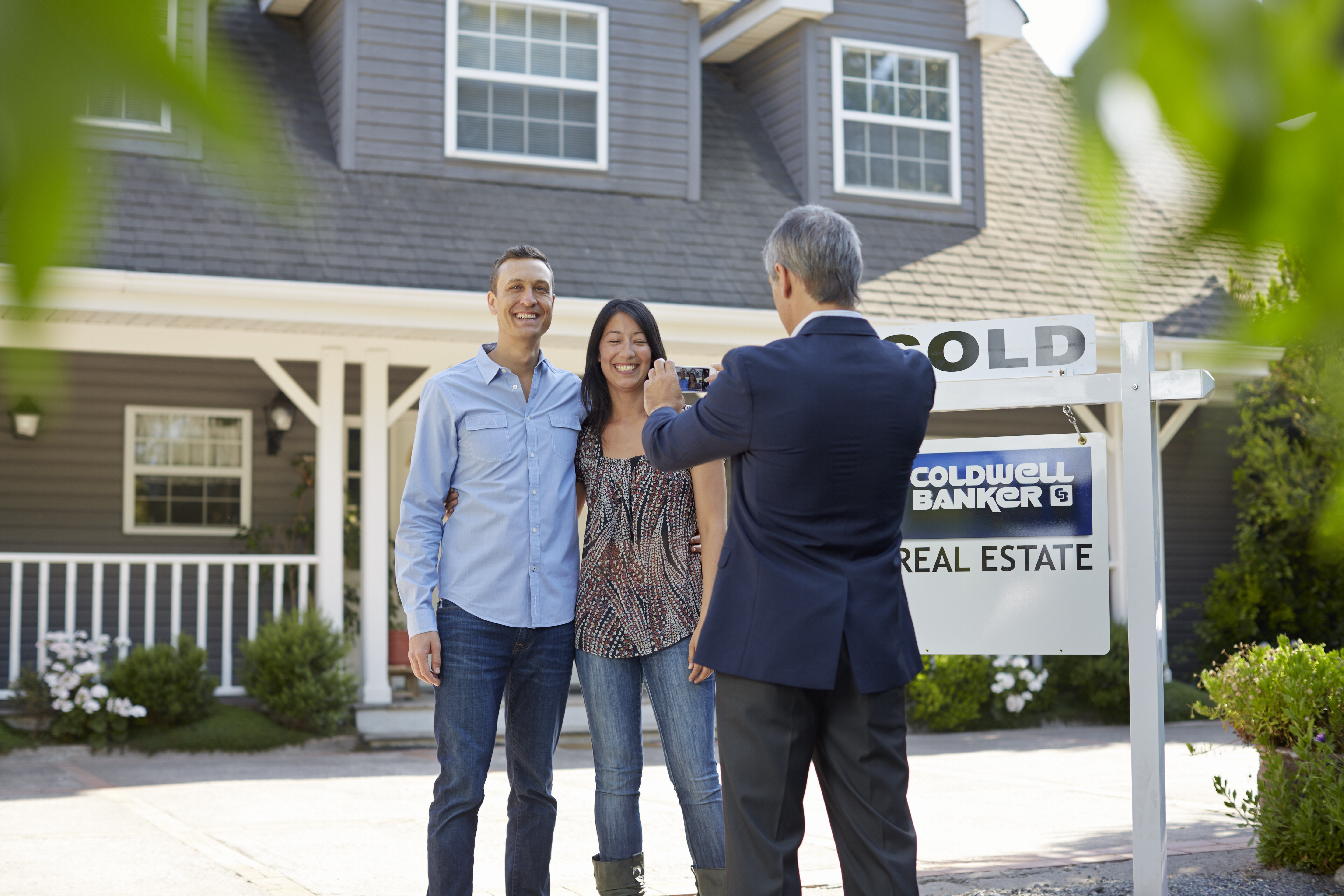5 Essential Tips for Homebuying - Realtor taking picture of home buyers.