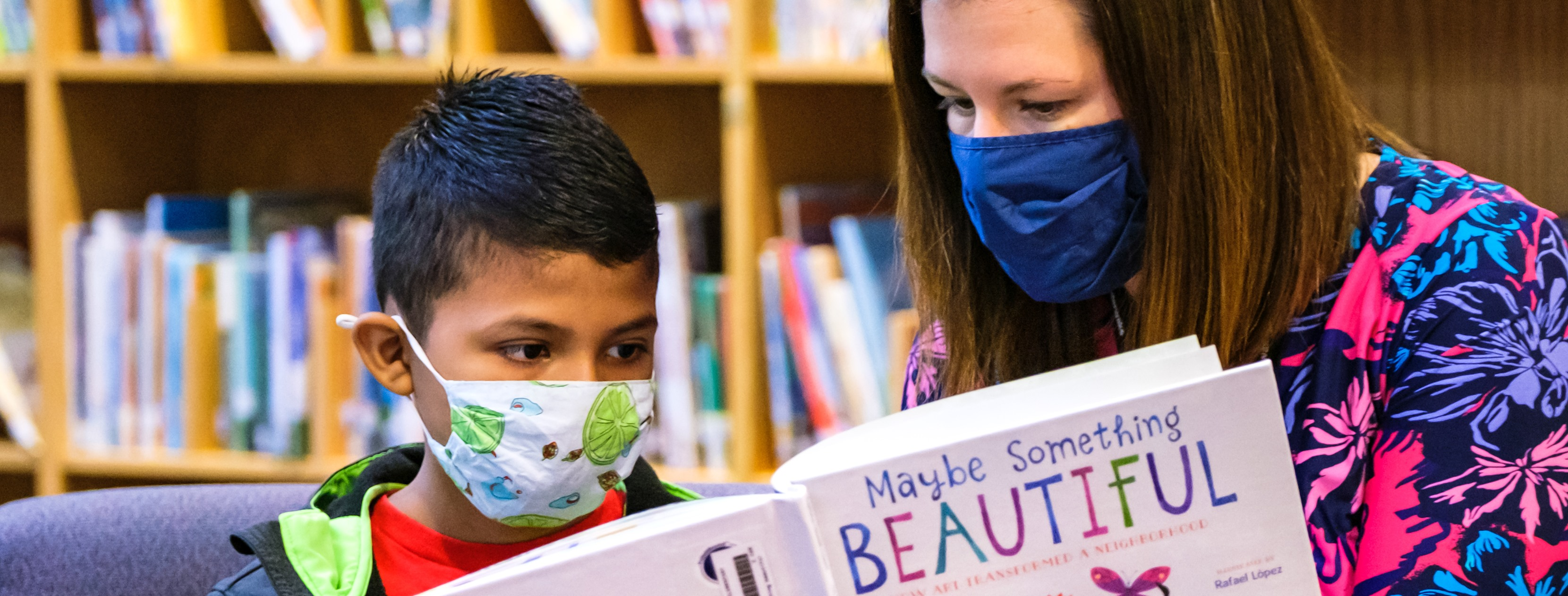 WCSS student reading with masks with teacher