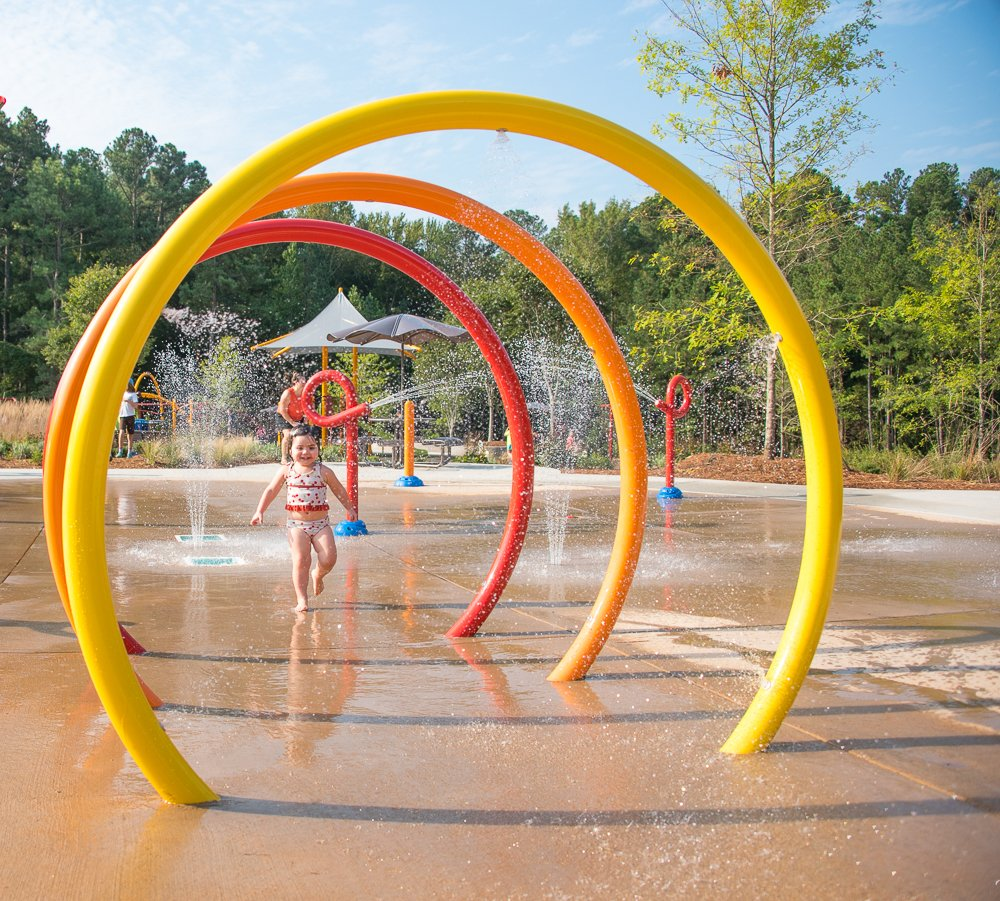 girl running through the sprayground at Jack Smith park in Cary