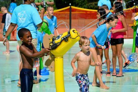 kids outside squirting water at the splash pad at Fuquay Varina's park