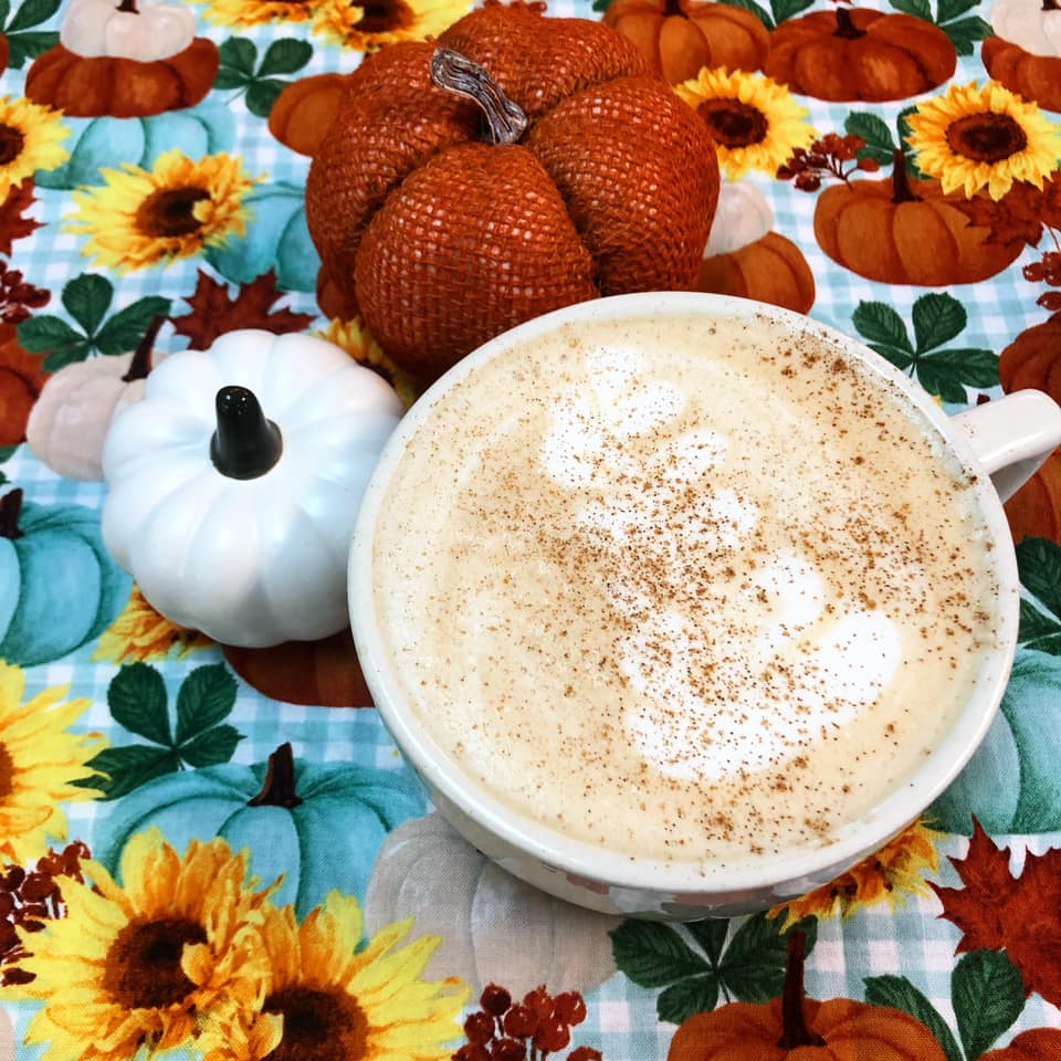 Living Raleigh Durham Featured Pumpkin Spice Drinks: NoRa Pumpkin Harvest Latte in a mug with a sunflower background
