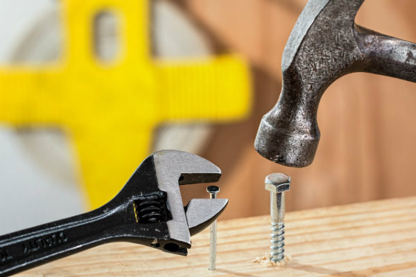 Using A hammer and a wrench to work on a board of wood
