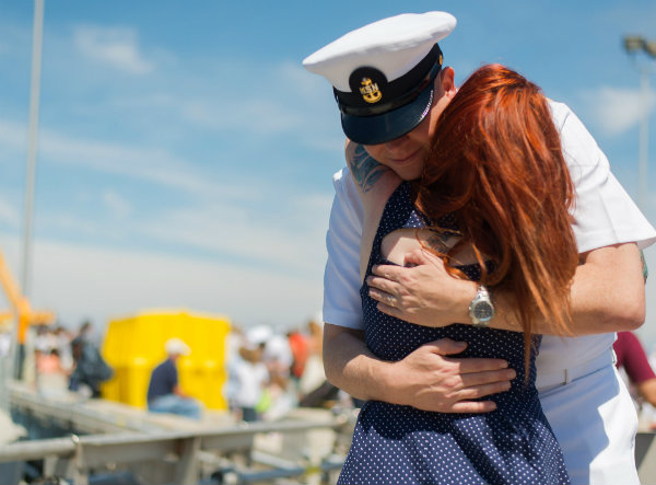 A Navy Officer Hugging his wife on the dock