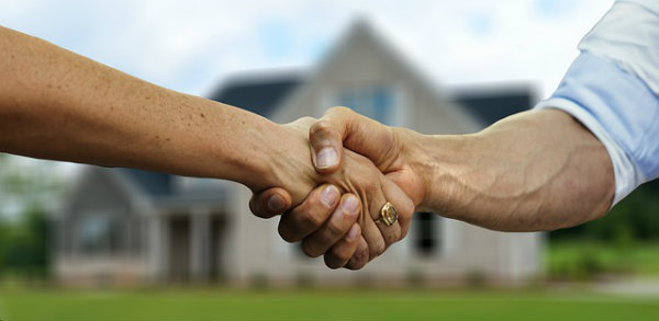 Real estate agent and seller shaking hand