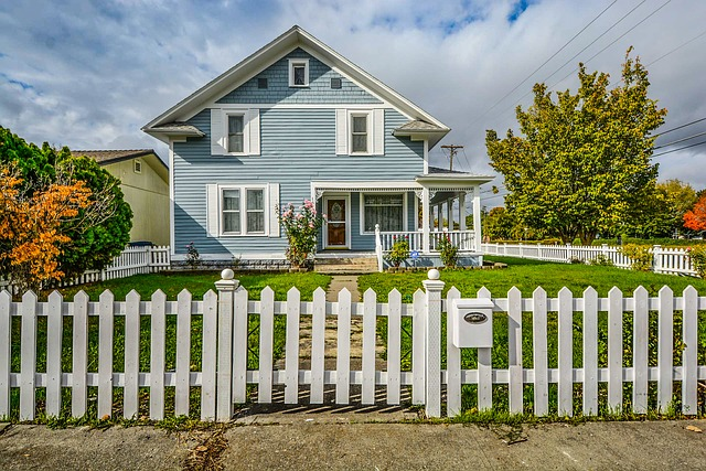 Big blue house with yard and white picket fence