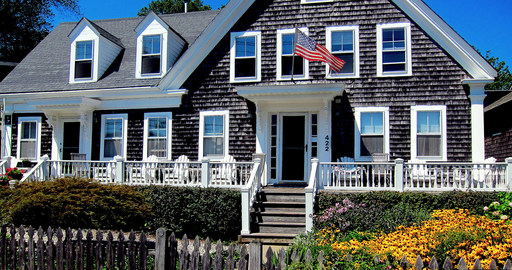 A Cape-style home with an American Flag in front