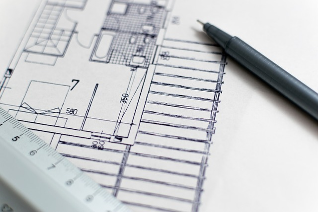 A pen laying on a blueprint of a house