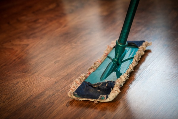 Hardwood floors being swept and cleaned with a dust mop