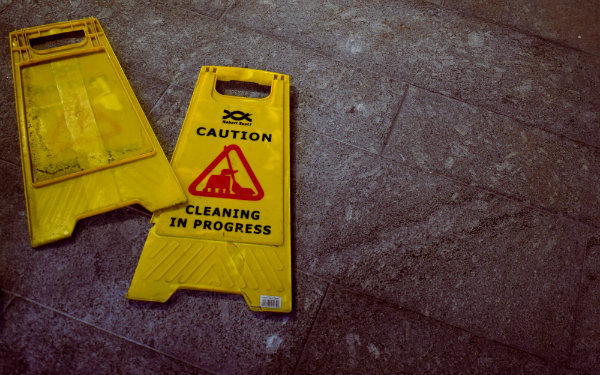 Yellow Caution sign laid out on floor for cleaning prep