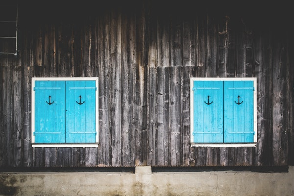 A wall of a home with two windows with turquoise shutters with anchor symbol etched on each