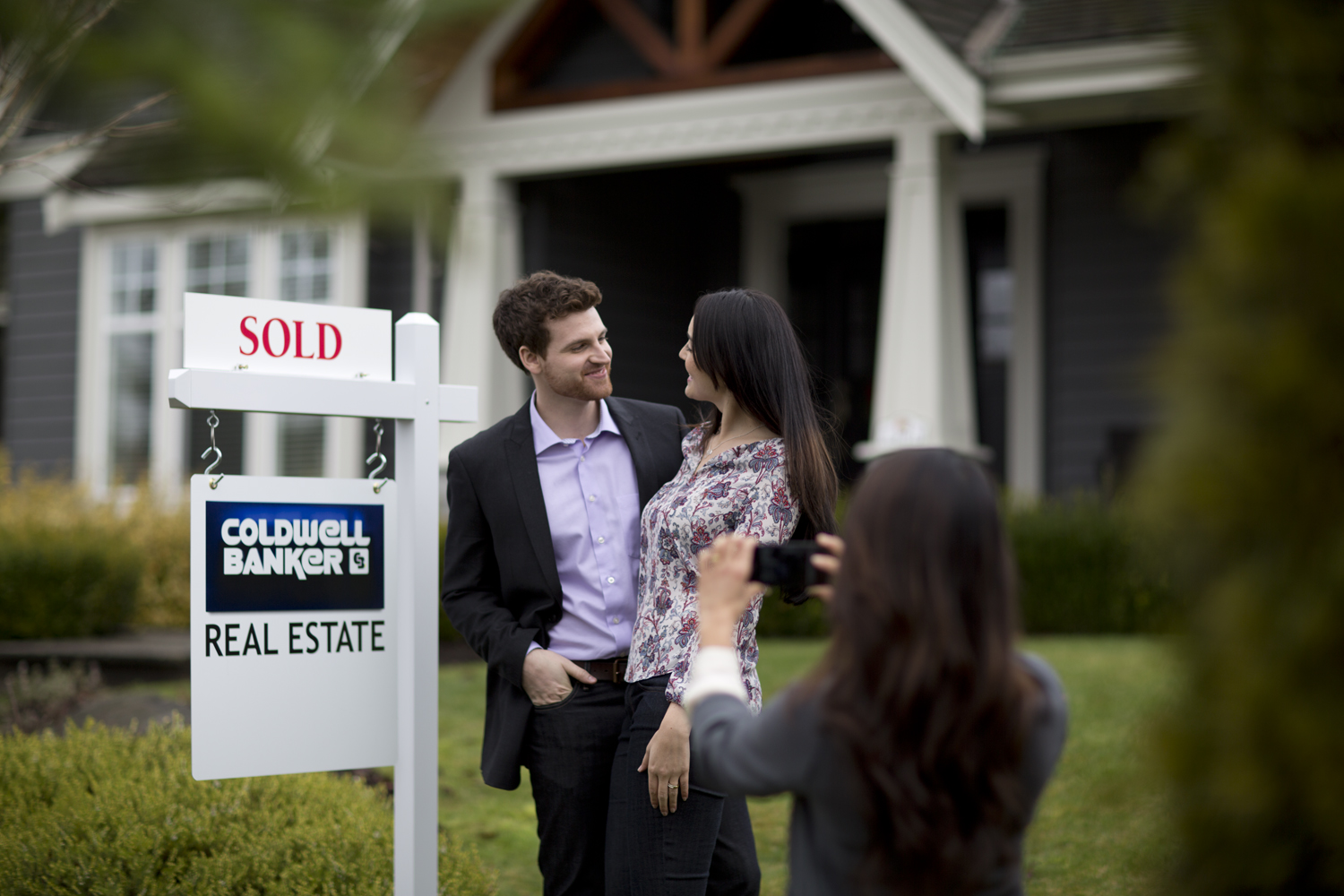 5 Essential Tips to Prepare for Buying a Home - realtor taking photo of new homeowners