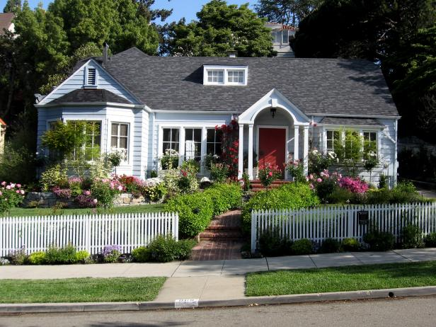 A light blue house with arched front door at the end of a brick walkway also boasts a front-yard cottage-style landscaped garden, complete with various flowers and plants, and a white picket fence.