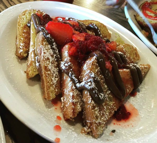 Plate of french toast covered in covered berries served at Sweet Life Bakery & Cafe