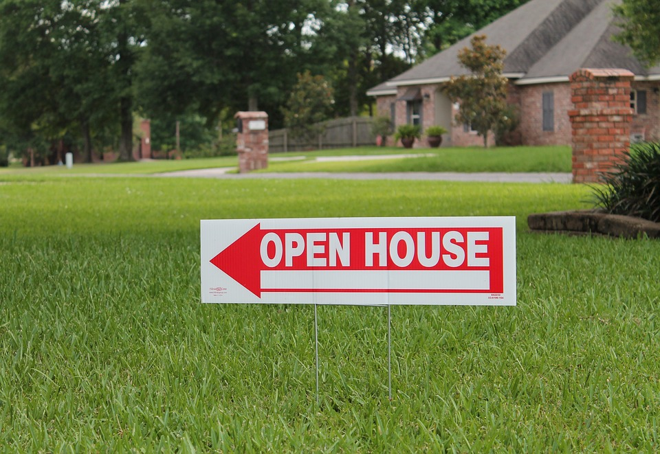 AN open House sign on the front lawn of a house