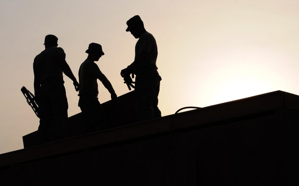 A group of construction workers working on the roof of a home