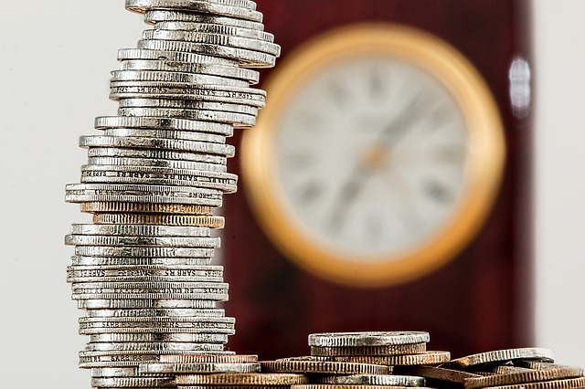 A stack of money sitting on a table with a clock in the background