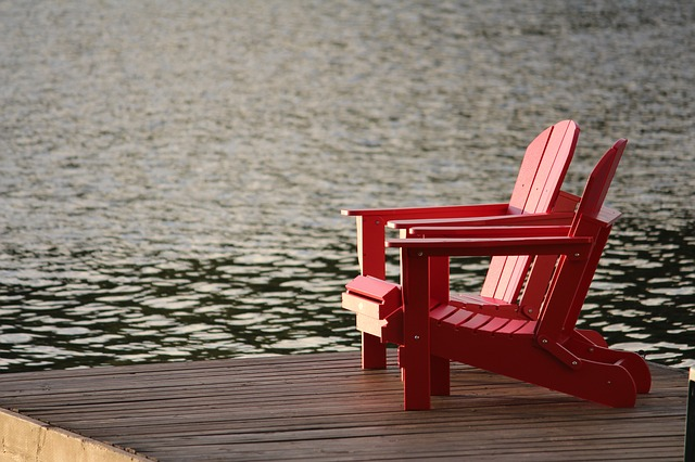 Two red chairs sitting on a dock by the ocean