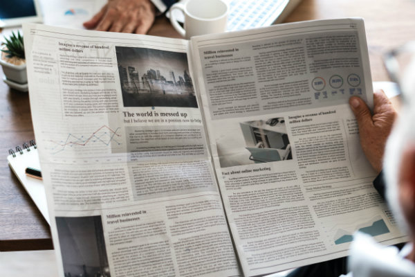 Someone reading about the market in a newspaper